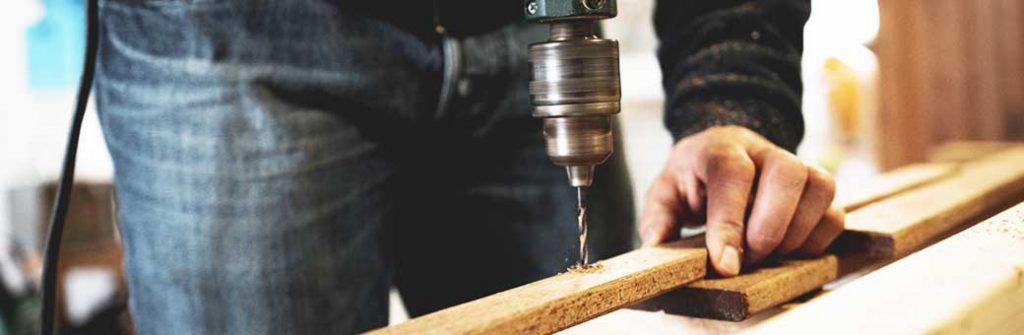 hombre que esta perforando madera con un taladro eléctrico