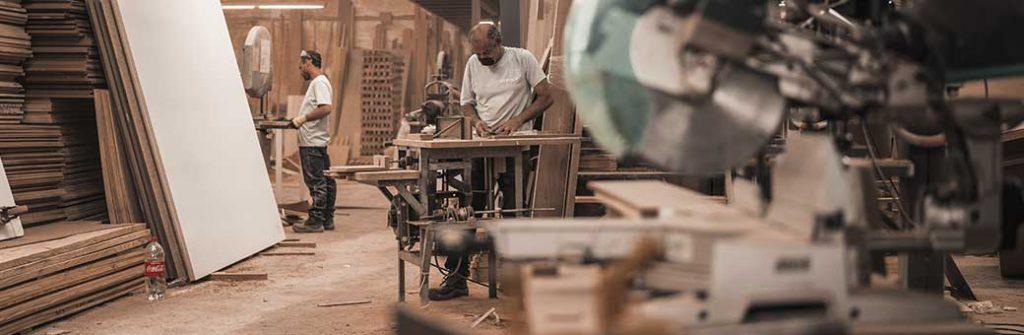 hombres trabajando en taller con maquinas y taladros electricos