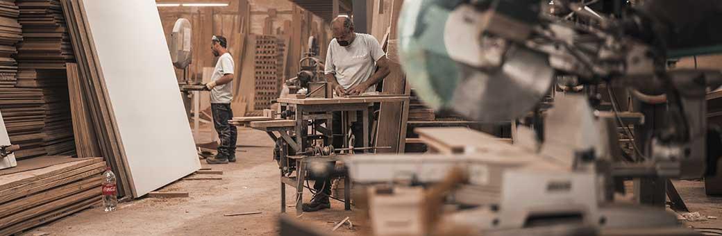hombres trabajando en taller con maquinas que utilizan taladros electricos