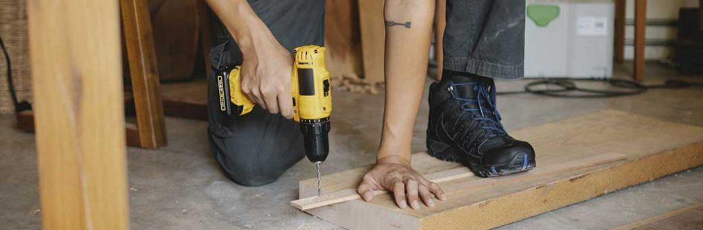 hombre taladrando madera con taladro inalambrico dewalt
